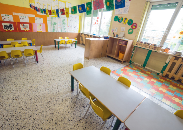 classromm of kindergarten with tables and small yellow chairs